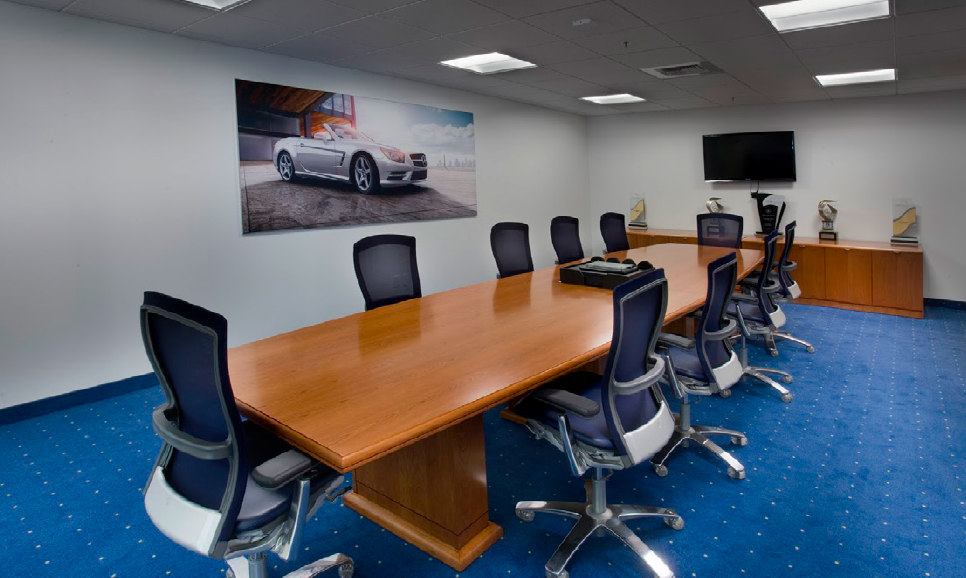 A typical meeting room with a rectangular table and a TV display at one end of the room.
